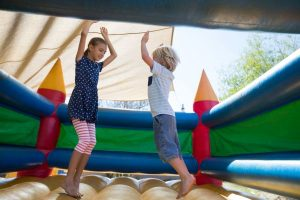 Happy siblings jumping on bouncy castle
